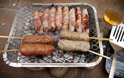 kebabs and sausages cooking on disposable bbq