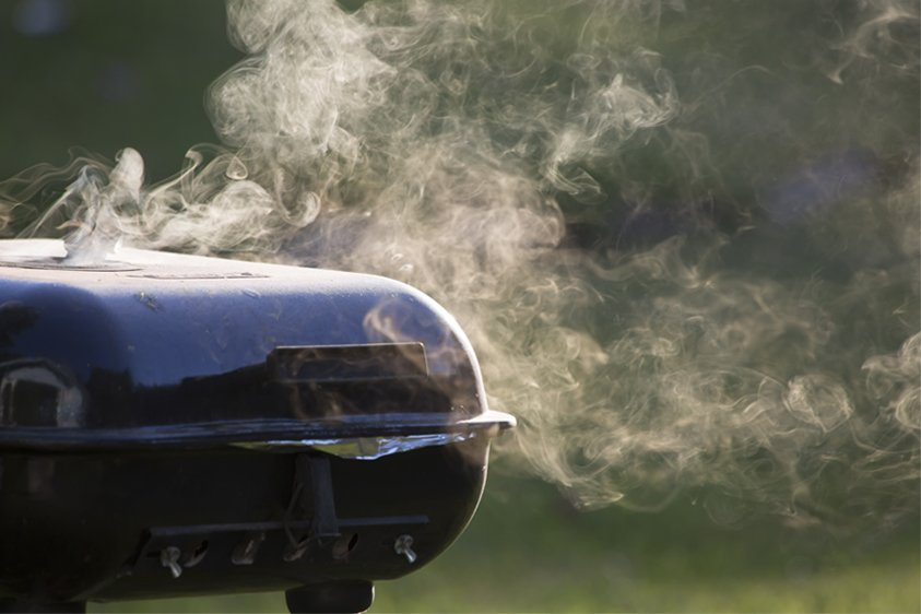 A kettle barbecue with smoke coming from it