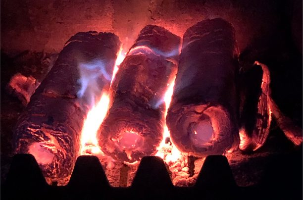 Compressed heat logs burning in grate