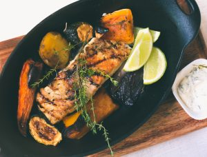 A perfectly grilled salmon fillet from a BBQ menu lies on a plate
