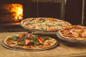 Three perfectly made pizzas lie in view with pizza oven fuel burning in the distance