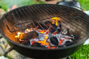 Flames from burning charcoal appear after lighting a BBQ