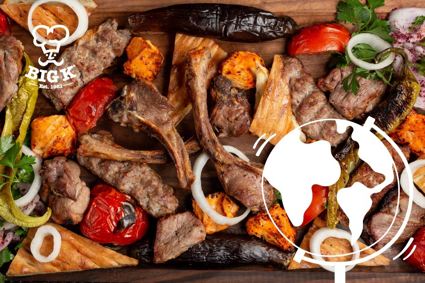 A selection of perfectly cooked BBQ meats and vegetables lie on a wooden surface
