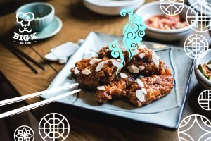 Perfectly crisp Korean BBQ chicken wings rest on a square plate