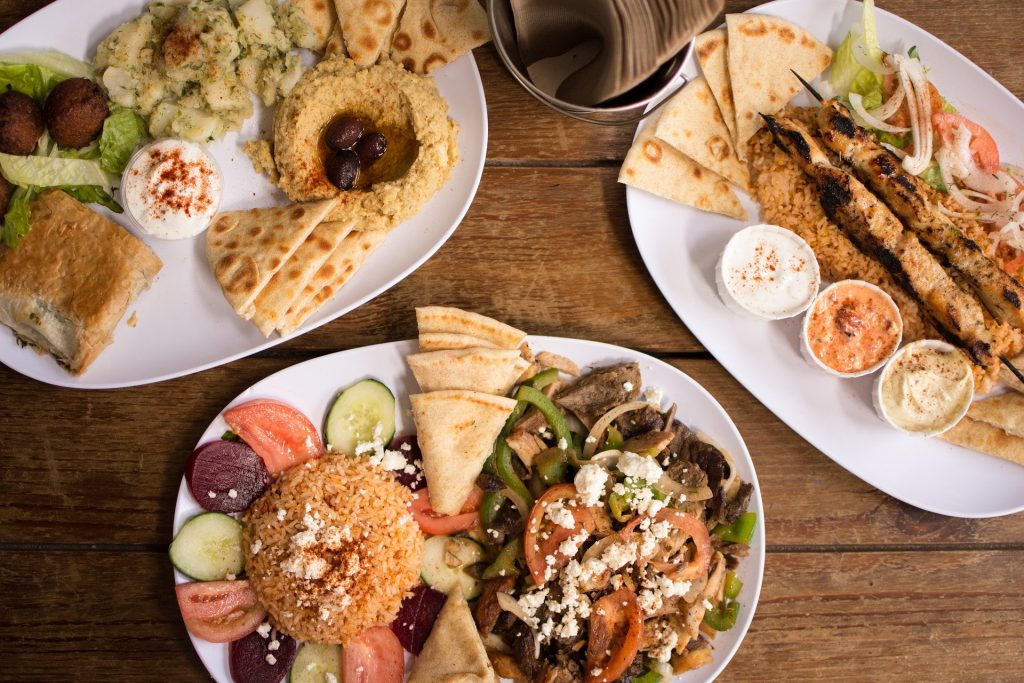 A Greek BBQ feast is ready and plated on a table, with dishes of souvlakia skewered meats, pita bread, salad and rice