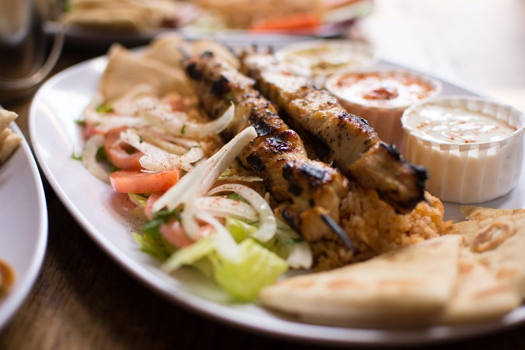 A Greek BBQ dish of skewered souvlakia meat lies on a plate with onions, pita bread and salad