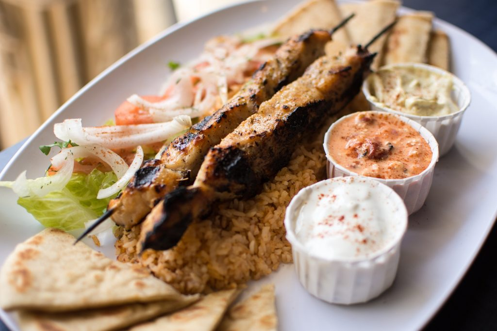 A close up of the perfect Greek BBQ plate consisting of skewered meat souvlakia, rice and pita bread.