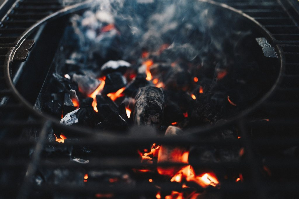 Flames rise out of a burning charcoal pile in a charcoal BBQ