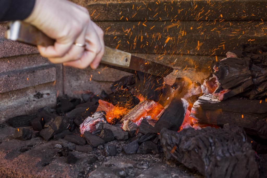 A hand holding tongs moves around burning charcoal in a charcoal BBQ