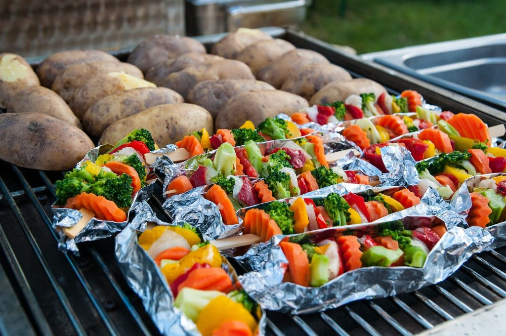A healthy selection of vegetable skewers and potatoes lies ready for the BBQ grill