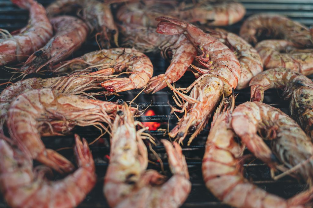 Perfectly cooked shrimp lie in the barbecue grill