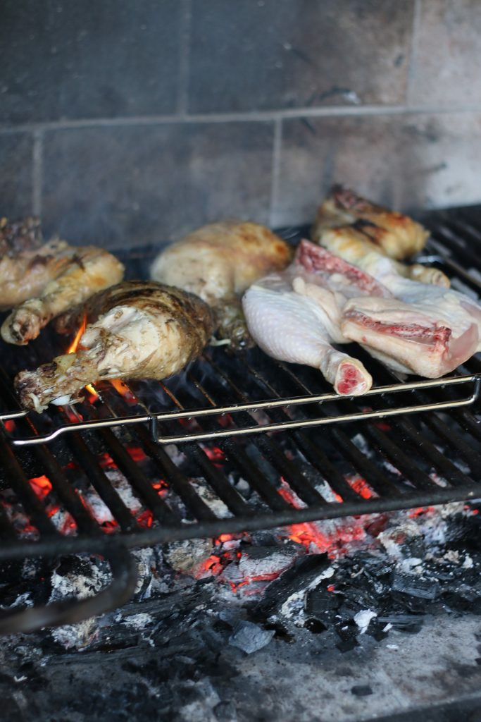 Chicken pieces cook within a charcoal barbecue grill