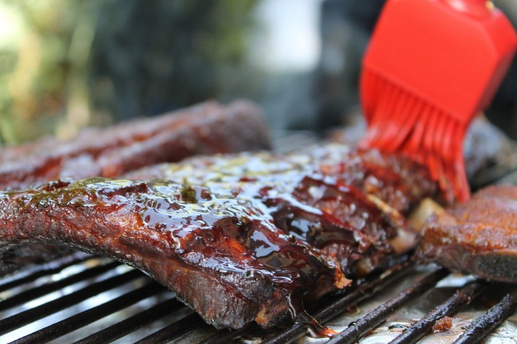 A brush slathers barbecue sauce over a rack of ribs on a grill