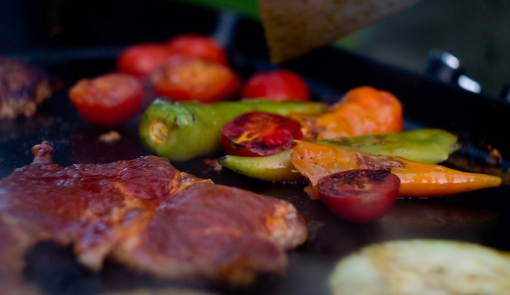 Meat and vegetables lie on the grill during a BBQ