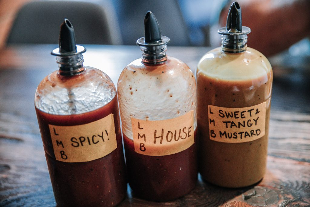 Three homemade bottles filled with barbecues sauce and other sauces are placed side by side on a table