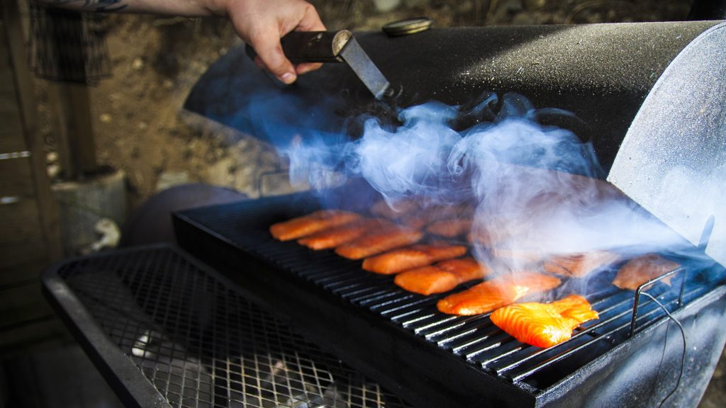 Fish pieces lie within a charcoal barbecue smoker surrounded by smoke
