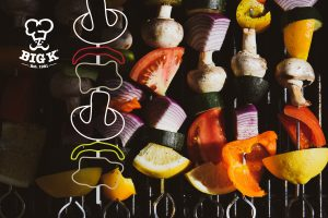 BBQ food skewers of vegetables are prepared to grill, lying on a grate