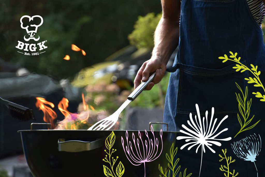 A man's garden barbecue is in full swing with flames rising off the grill and greenery all around