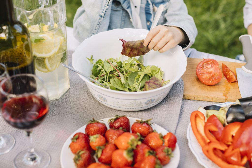 A vegetarian spread of salad and strawberries plus drinks sit on a table as the garden barbecue begins