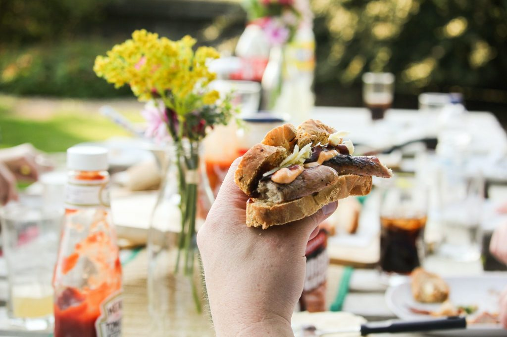 A sausage sandwich is being held up against a colourful garden barbecue backdrop.