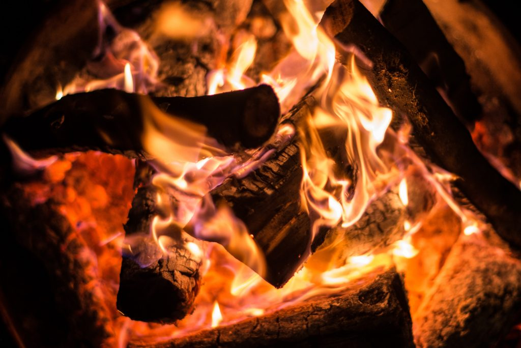 Seasoned logs burn and glow in an open fire