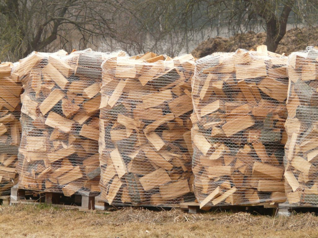 Seasoned logs lie chopped and stacked in bags ready to be sold