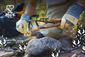A man uses some string as a firelighter to light an outdoor fire of sticks