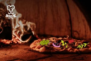 Pizza oven fuel burns brightly in a pizza oven illuminating a crispy pizza cooked to perfection