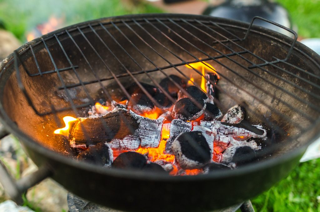 Lumpwood charcoal burns in a shallow grill base with yellow and orange flames
