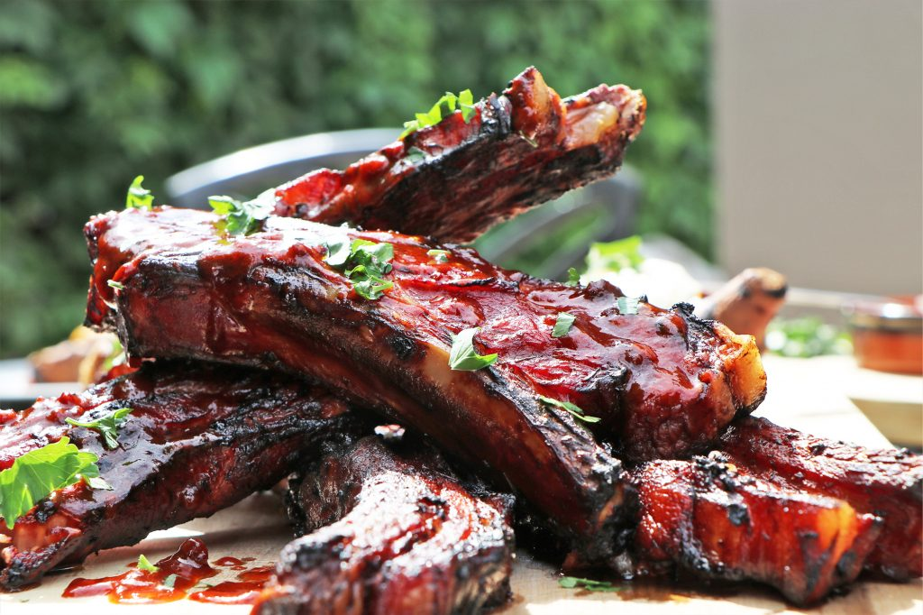Ribs are one of the best BBQ recipes around. This pile of reddish BBQ ribs is garnished and ready to eat on the plate.