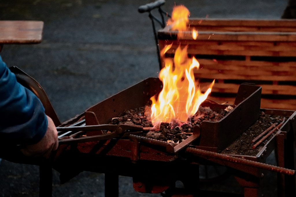 A man starting a BBQ controls the orange flames rising from his pile of thinly spread charcoal