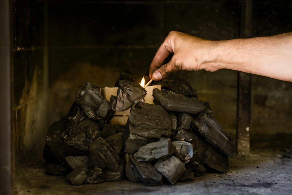A hand lights some kindling within a charcoal stack to complete the second step in lighting a BBQ.