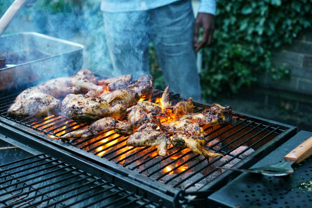 A man is cooking chicken wings on an outdoor barbecue grill as flames lick up the side of the chicken pieces