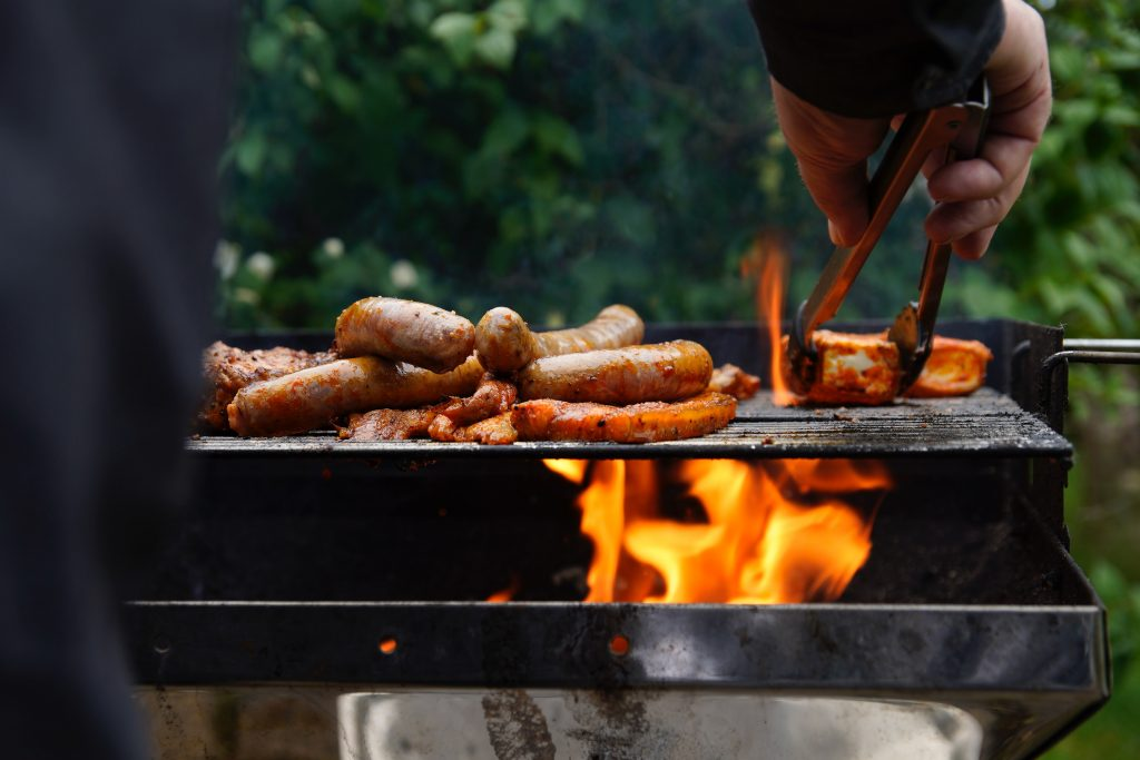 A man is cooking three different types of sausage on his outdoor barbecue grill.