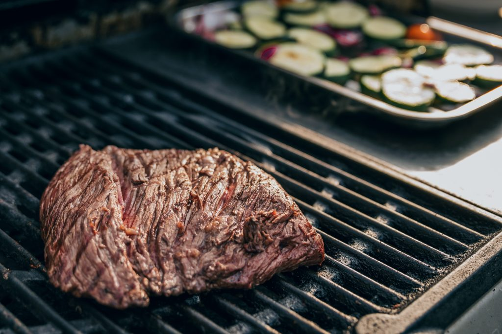 A cut of medium rare beef lies on an American BBQ smoker grill See copy above for insertion point in red