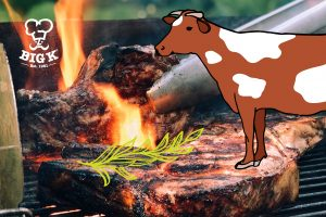 Two barbecue steaks lie on the grill surrounded by flames