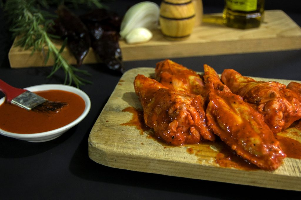 Perfectly prepared barbecue chicken is covered in barbecue sauce positioned on a wooden platter