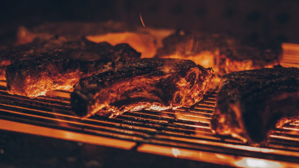 Three barbecue steaks are cooking on a grill engulfed in yellow flames