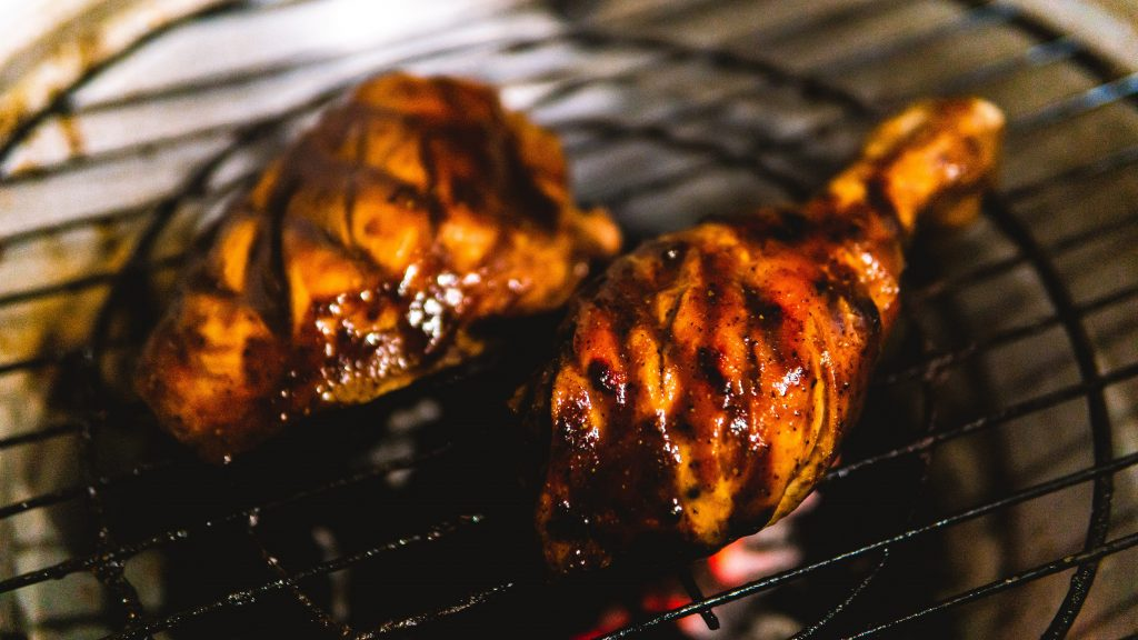 A barbecue chicken thigh and leg are cooking on a barbecue over hot charcoal