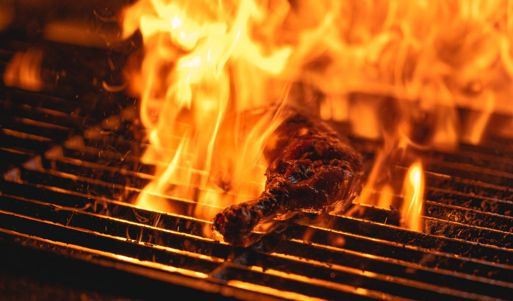 Barbecue chicken lies on a grill surrounded by orange flames