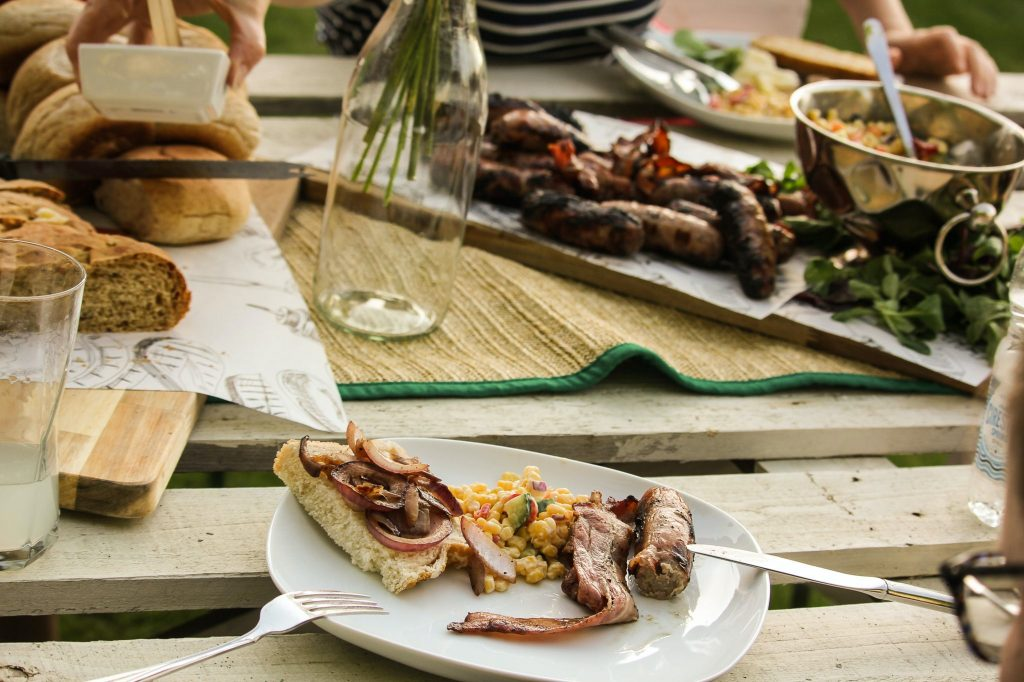 A BBQ party spread of delicious meats and vegetables lies on a table waiting to be eaten