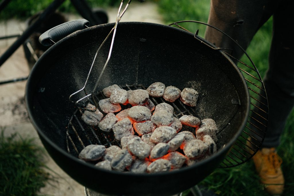 A beautiful mound of charcoal burns red hot in a barbecue at a garden BBQ