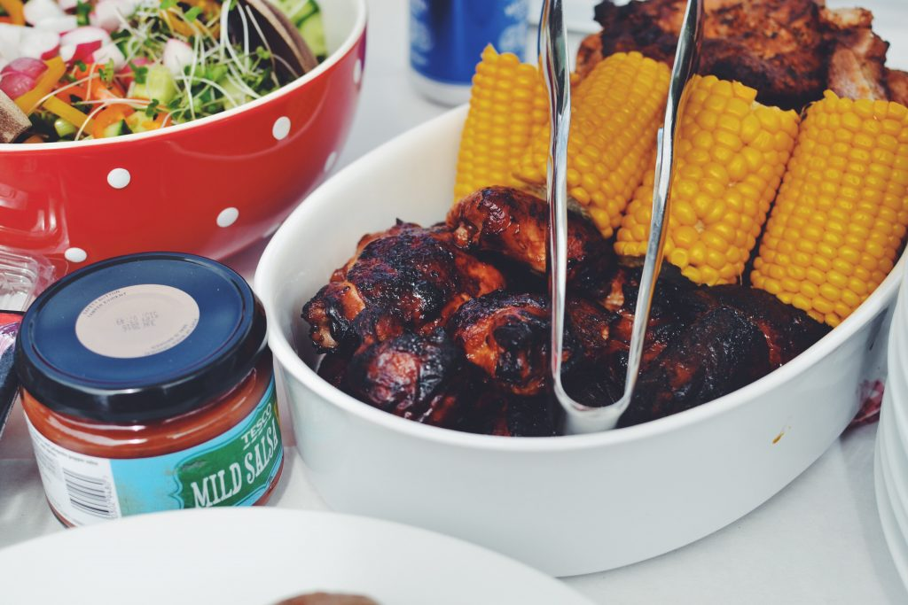 A bowl of BBQ chicken and corn on the cob lie on atable at a BBQ party.