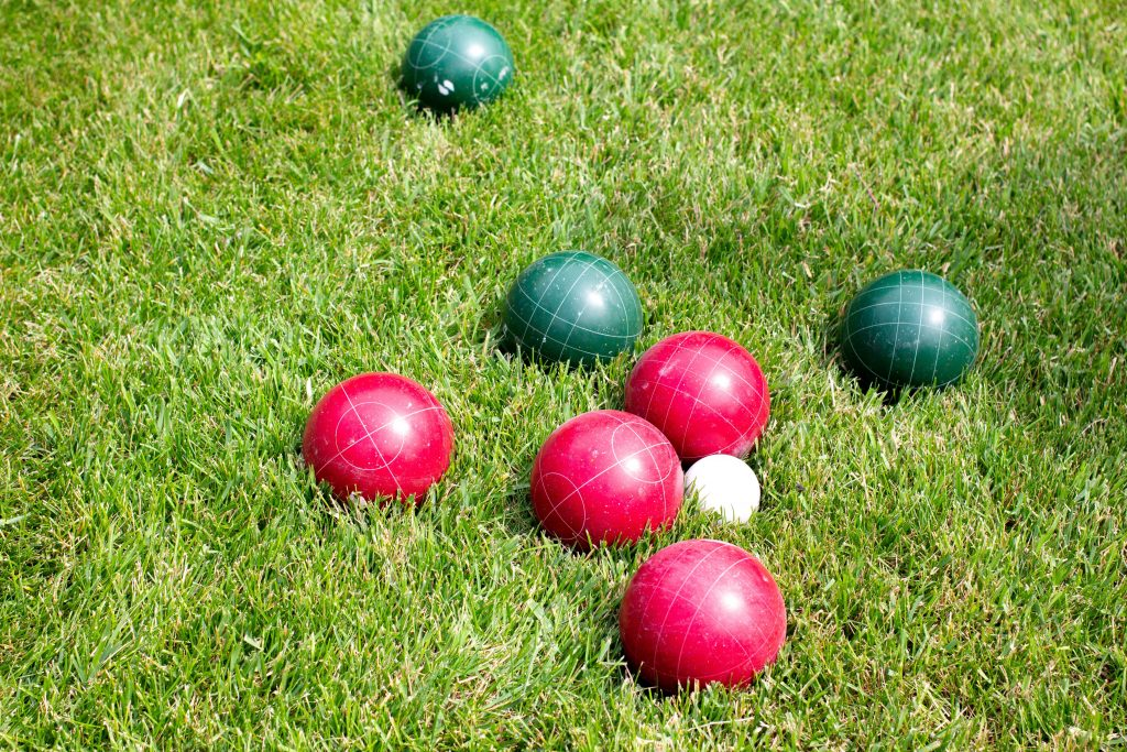 Some plastic boules lie on a green lawn as the perfect BBQ party entertainment.
