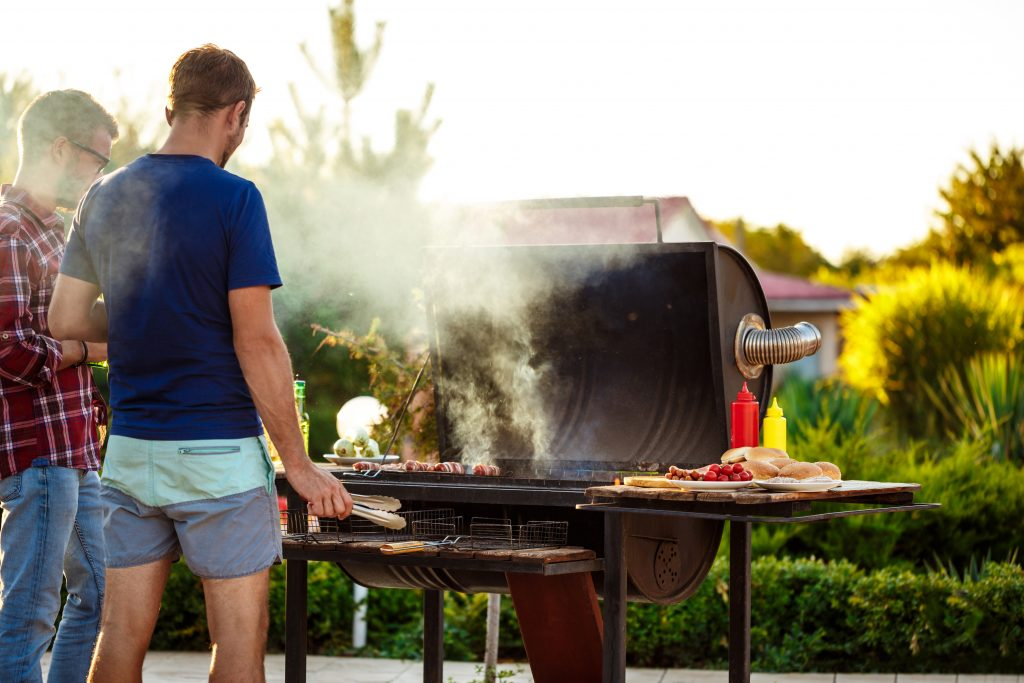 Two men at a garden BBQ stand by a grill with some sausages wrapped in bacon grilling on the grill.
