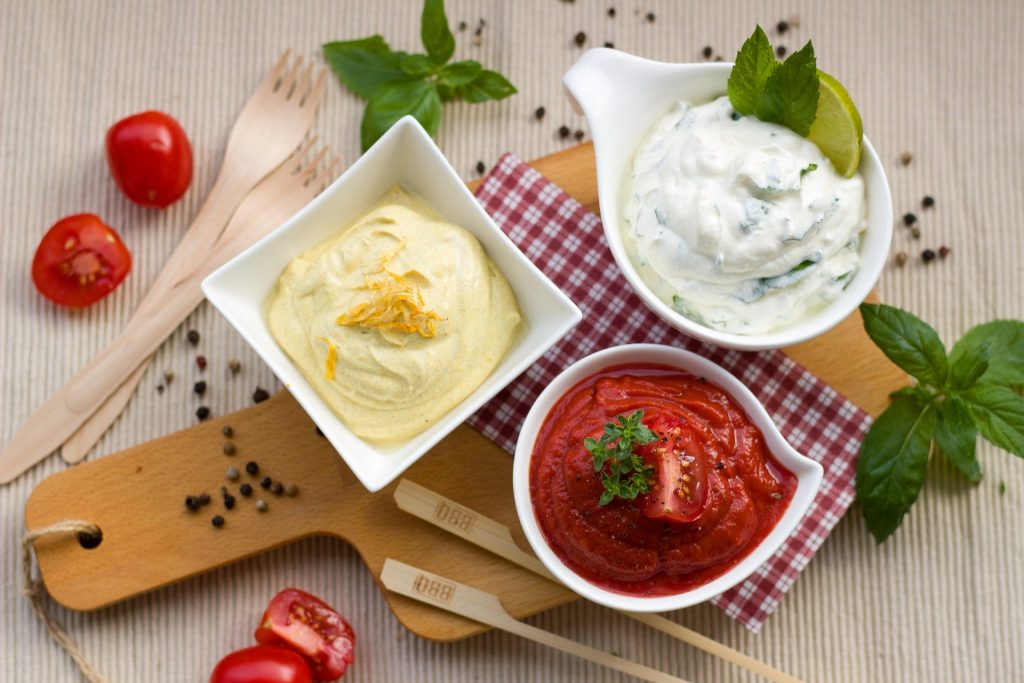 Three dips including mayonnaise and BBQ sauce sit freshly prepared on a table ready for serving.