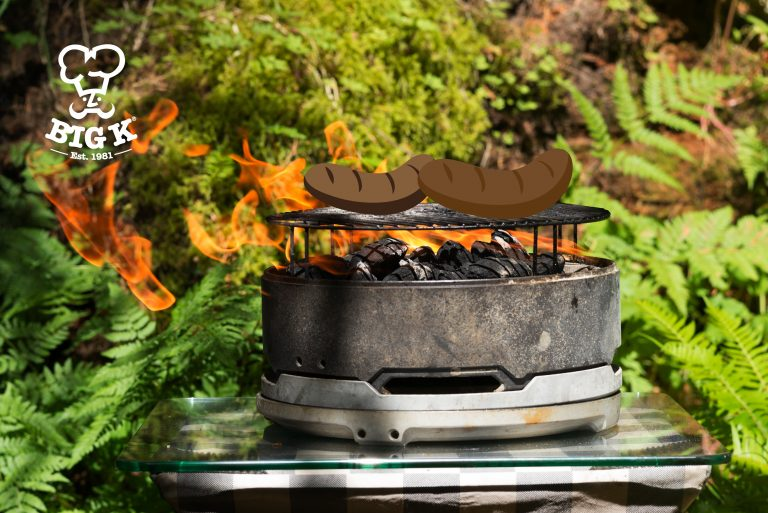 A grill full of charcoal emits yellow flame set against a leafy woody scene – the perfect camping bbq setup