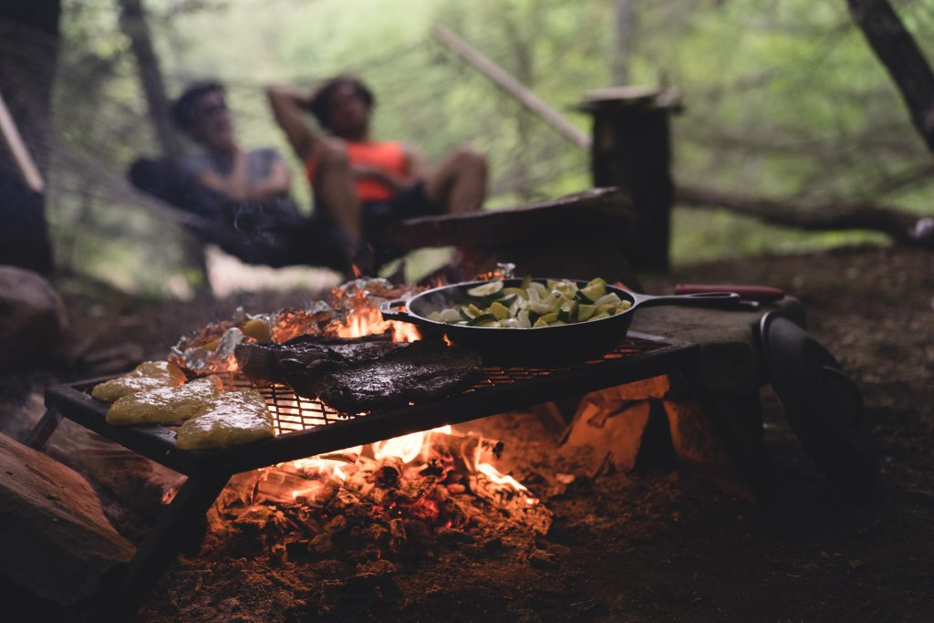 Vegetables and steak cook on an outdoor camping BBQ grill while two people sit in a hammock and talk surrounded by the forest