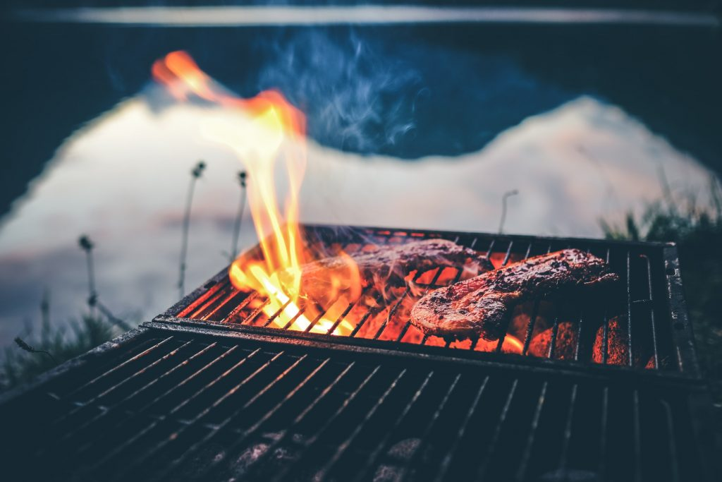 two steaks cook on a camping BBQ grill with orange flames