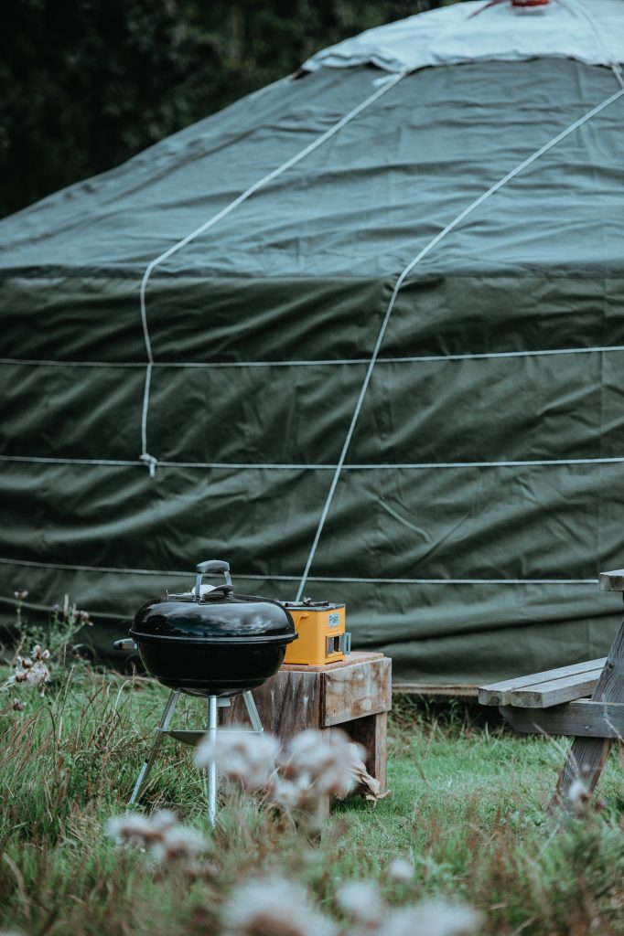 A camping BBQ stands in fornt of a camping tent in a field ready for use